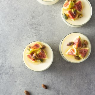 Overhead shot of four glasses of buttermilk goat cheese panna cotta topped with figs, pistachios and honey on a light, grey textured surface.