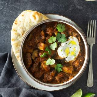 Overhead shot of a bowl of lamb curry with eggplant and tomatoes topped with cilantro and yogurt sauce surrounded by naan bread, a bowl of yogurt sauce, a fork, lime wedges and a dish towel on a dark grey, textured surface.