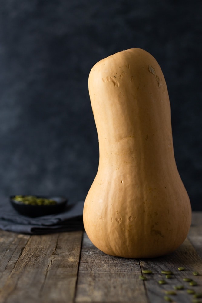 Straight on shot of a whole raw butternut squash standing up on a grey wood surface with a dark textured background with a small bowl of pepitas and a dish towel in the background.