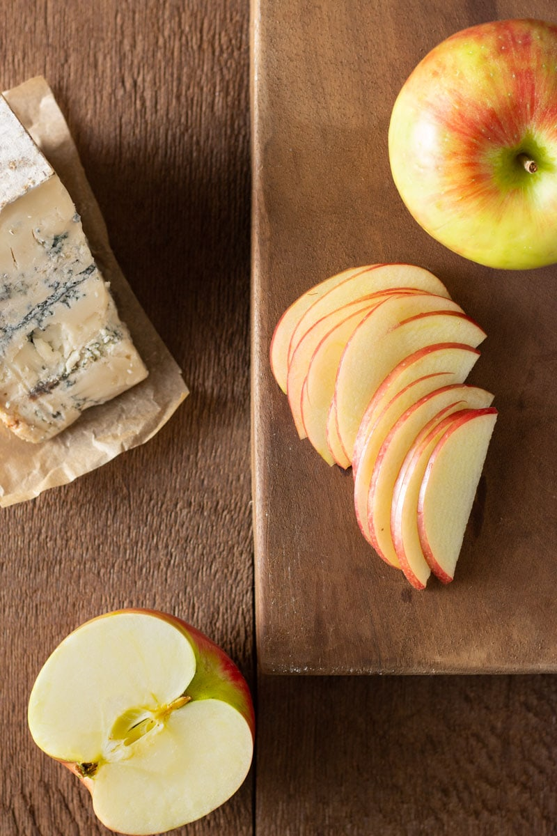 Overhead shot of sliced apples on a wooden cutting board near a wedge of blue cheese on a dark wood surface.