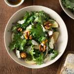 Overhead shot of a bowl of Kale Apple Salad with Blue Cheese, Maple Glazed Walnuts and balsamic dressing on a dark wood surface surrounded by a small bowl of dressing, a wedge of blue cheese and a bowl of kale.