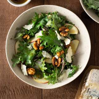 Overhead shot of a bowl of Kale and Apple Salad with Blue Cheese, Maple Glazed Walnuts and balsamic dressing on a dark wood surface surrounded by a small bowl of dressing, a wedge of blue cheese and a bowl of kale.