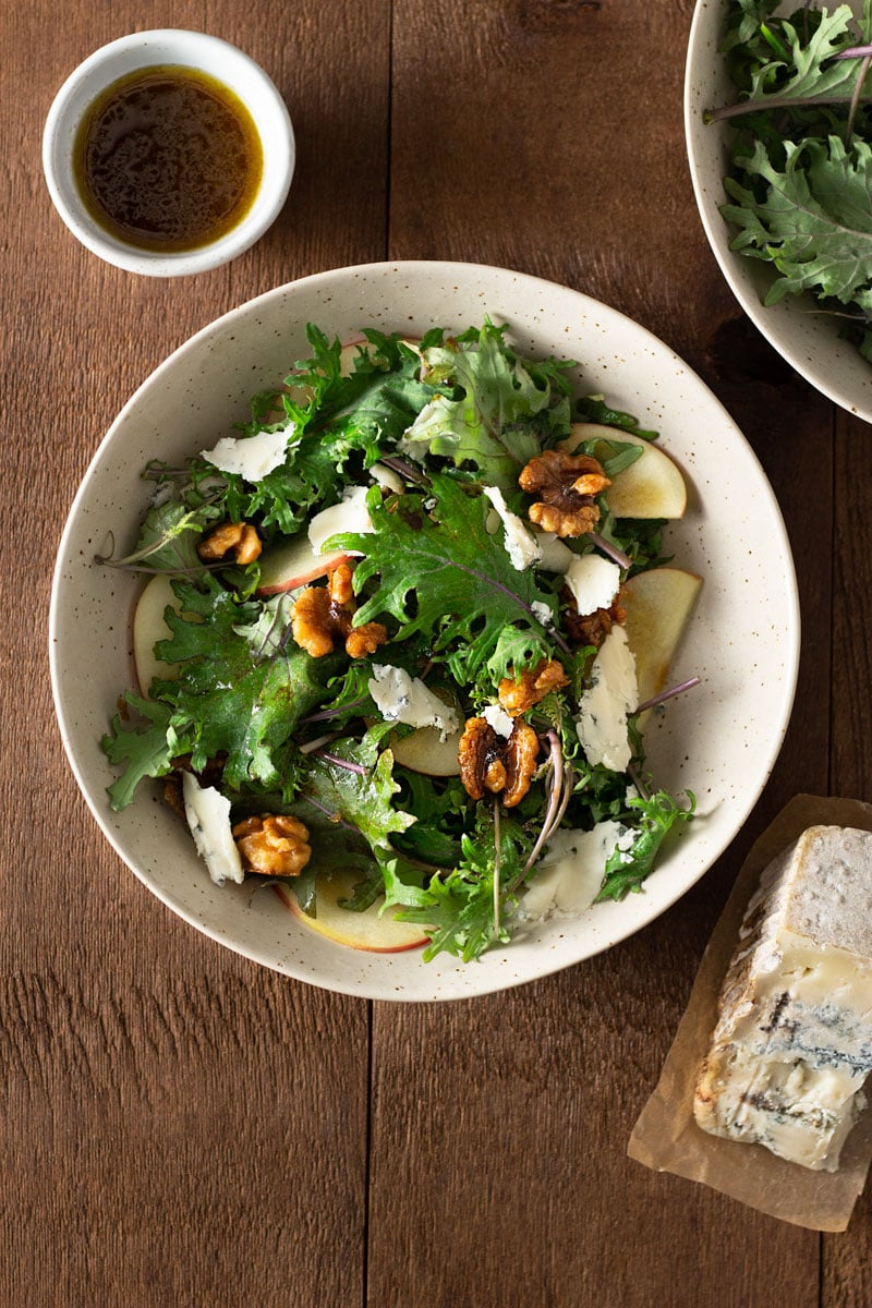 Overhead view of a bowl of Kale and Apple Salad with Blue Cheese, Maple Glazed Walnuts and balsamic dressing on a dark wood surface surrounded by a small bowl of dressing, a wedge of blue cheese and a bowl of kale.