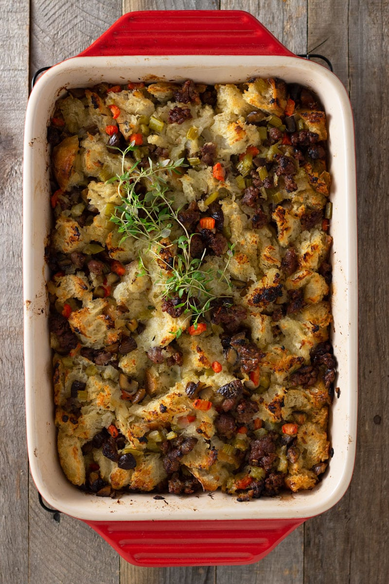 Overhead view of a red baking tray of Sausage Chestnut Stuffing topped with fresh thyme on a grey wood surface.