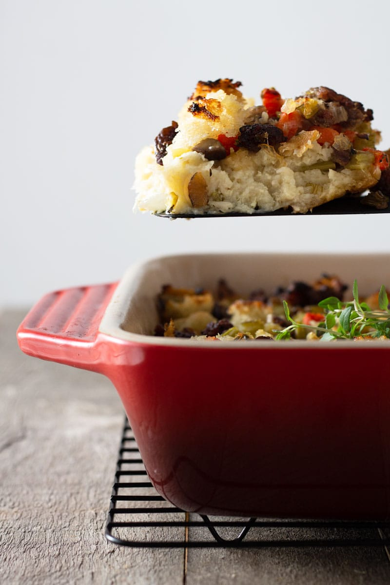 Straight on view of a spatula with a serving of Sausage Chestnut Stuffing being held over a red baking dish of stuffing on a grey wood surface.