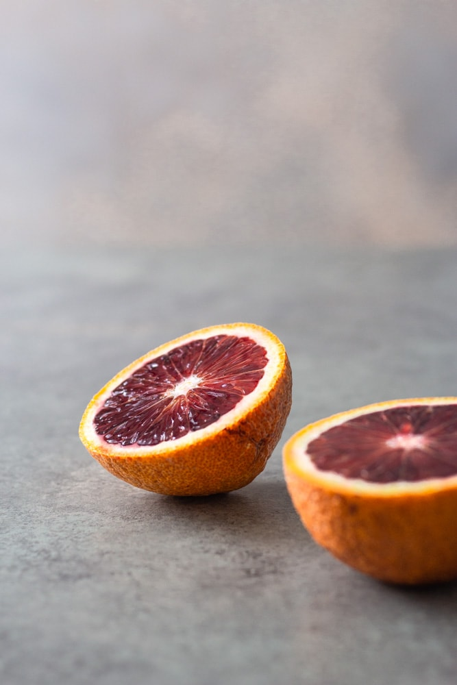 Straight on view of two halves of a blood orange on a light grey textured surface with a blue grey background.