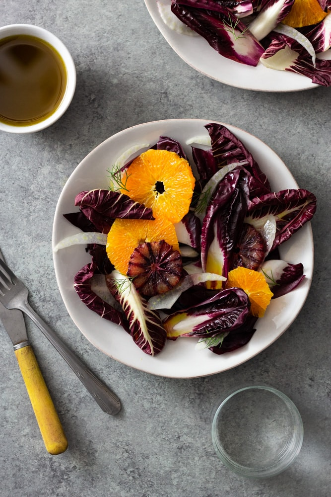 Overhead view of an Orange and Fennel Salad with Radicchio, blood orange, fennel fronds and a sherry vinaigrette on a white plate surrounded by a small bowl of dressing, another plate of salad, a fork, a knife and a glass of water on a grey, textured surface.