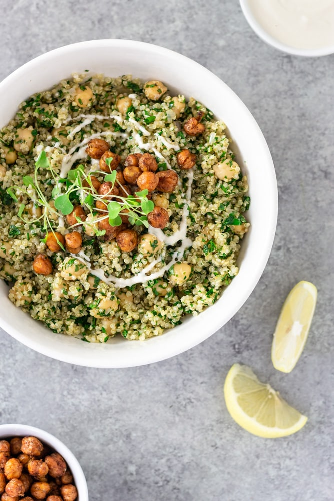 Overhead view of a bowl of Herbed Chickpea and Quinoa Salad with Tahini Yogurt topped with spiced, crispy chickpeas and microgreens, surrounded by lemon wedges and bowls of tahini yogurt and crispy chickpeas on a light grey textured surface.