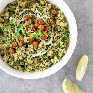 Overhead view of a bowl of Quinoa and Chickpea Salad topped with crispy chickpeas and tahini yogurt, surrounded by lemon wedges, and salad ingredients on a light grey textured surface.