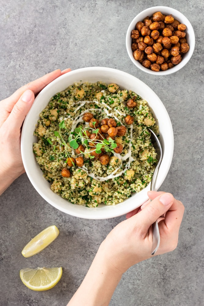 Overhead view of hands sticking a spoon into a bowl of Herbed Chickpea and Quinoa Salad with Tahini Yogurt topped with spiced, crispy chickpeas and microgreens, surrounded by lemon wedges and a bowl of crispy chickpeas on a light grey textured surface.