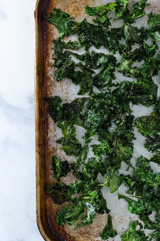 Overhead shot of a sheet tray of kale chips on a  marble surface.
