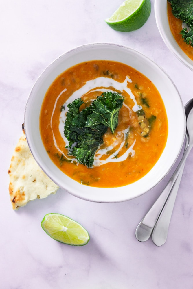 Overhead shot of a bowl of Thai Red Curry Lentil Soup topped with coconut milk and kale chips on a marble surface surrounded by lime wedges, naan bread and spoons.