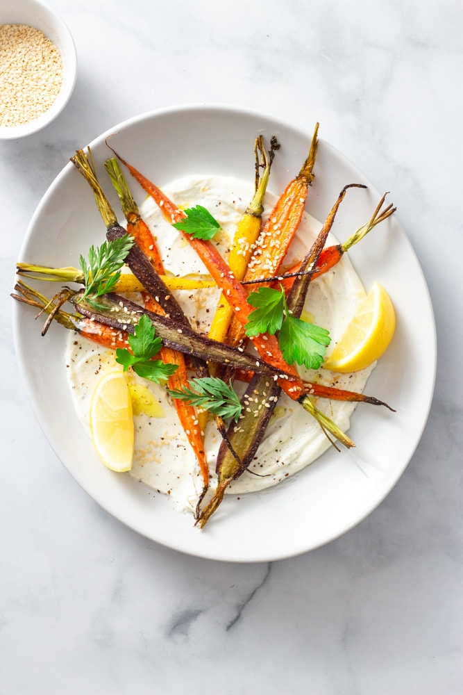 Overhead shot of a plate of sumac yogurt topped with mixed roasted heirloom carrots, topped with parsley and carrot top leaves, sesame seeds and sumac with lemon wedges on a marble surface.