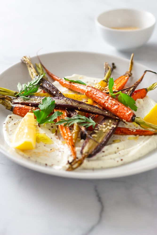 3/4 angled shot of a plate of sumac yogurt topped with mixed roasted heirloom carrots, topped with parsley and carrot top leaves, sesame seeds and sumac with lemon wedges on a marble surface.