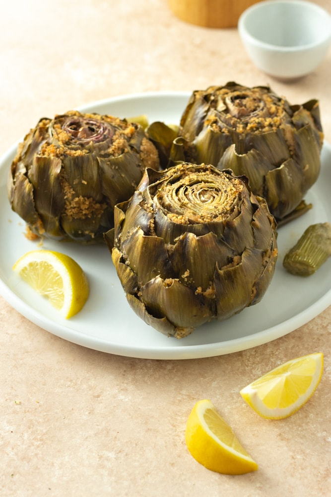 3/4 angled view of Italian Stuffed Artichokes filled with breadcrumbs, cheese, garlic and parsley on a white plate surrounded by lemon wedges, and bowls of salt and pepper on a beige textured surface.