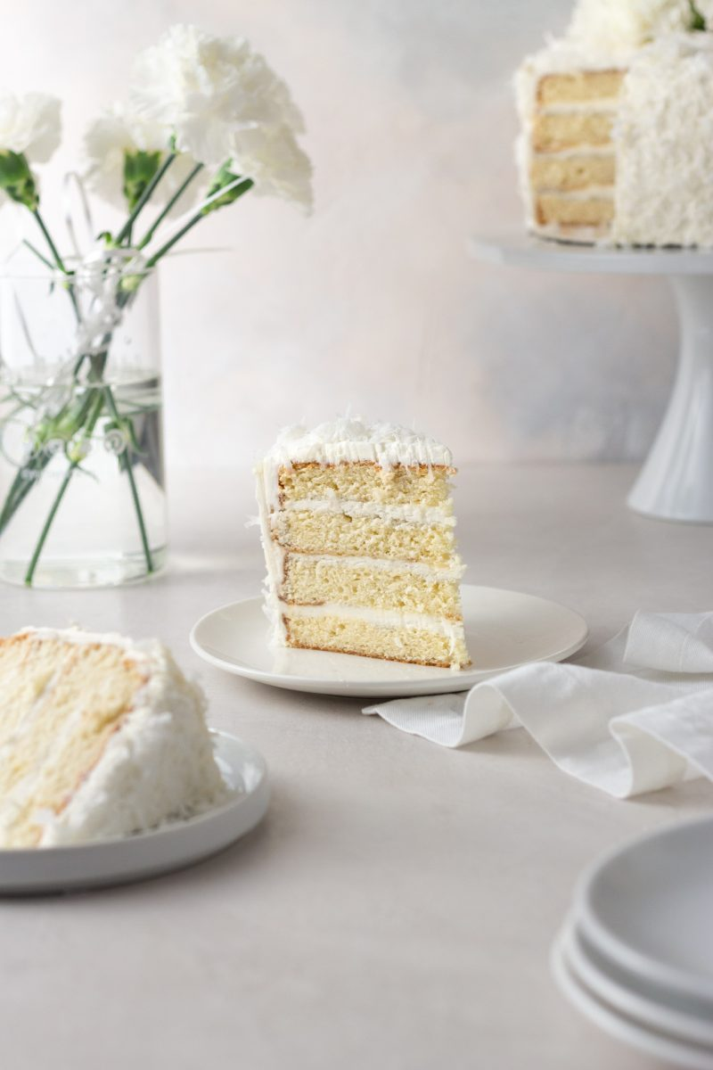 Straight on view of a slice of coconut layer cake with Swiss meringue buttercream on a plate surrounded by another slice of cake, plates, a napkin, a vase of white carnation flowers and the cake on a cake stand with a cream colored surface and light textured background.