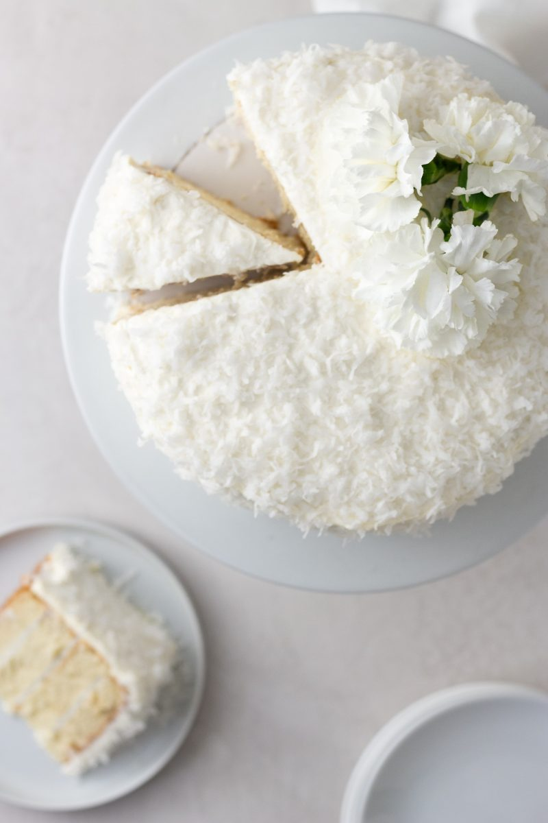 Overhead view of a sliced coconut layer cake with Swiss meringue buttercream on a cake stand topped with white carnation flowers with a cream colored surface and light textured background.