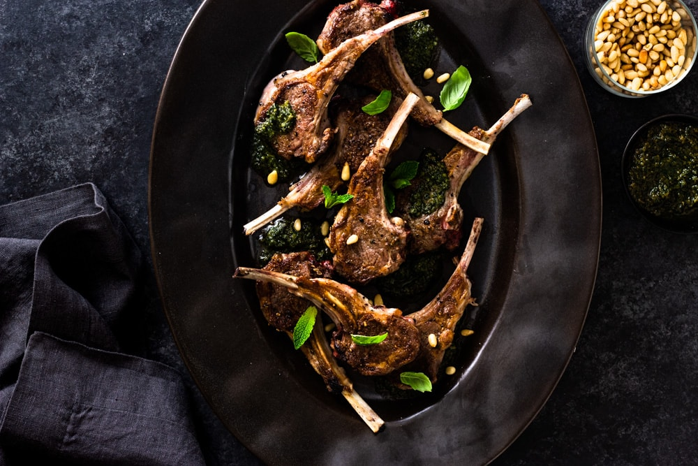 Overhead shot of a black serving dish with seared baby lamb chops, mint pesto, pine nuts and fresh herbs on a dark textured background.