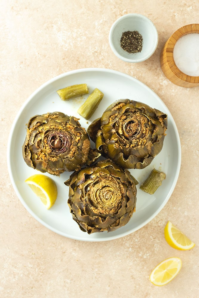 Overhead view of Italian Stuffed Artichokes filled with breadcrumbs, cheese, garlic and parsley on a white plate surrounded by lemon wedges, and bowls of salt and pepper on a beige textured surface.