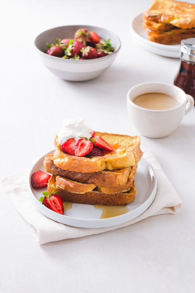 3/4 angled view of a stack of Brioche French Toast topped with macerated strawberries and whipped mascarpone cream on a white plate on a napkin on a white surface with strawberries, a cup of coffee, maple syrup and a plate of more French toast in the background.