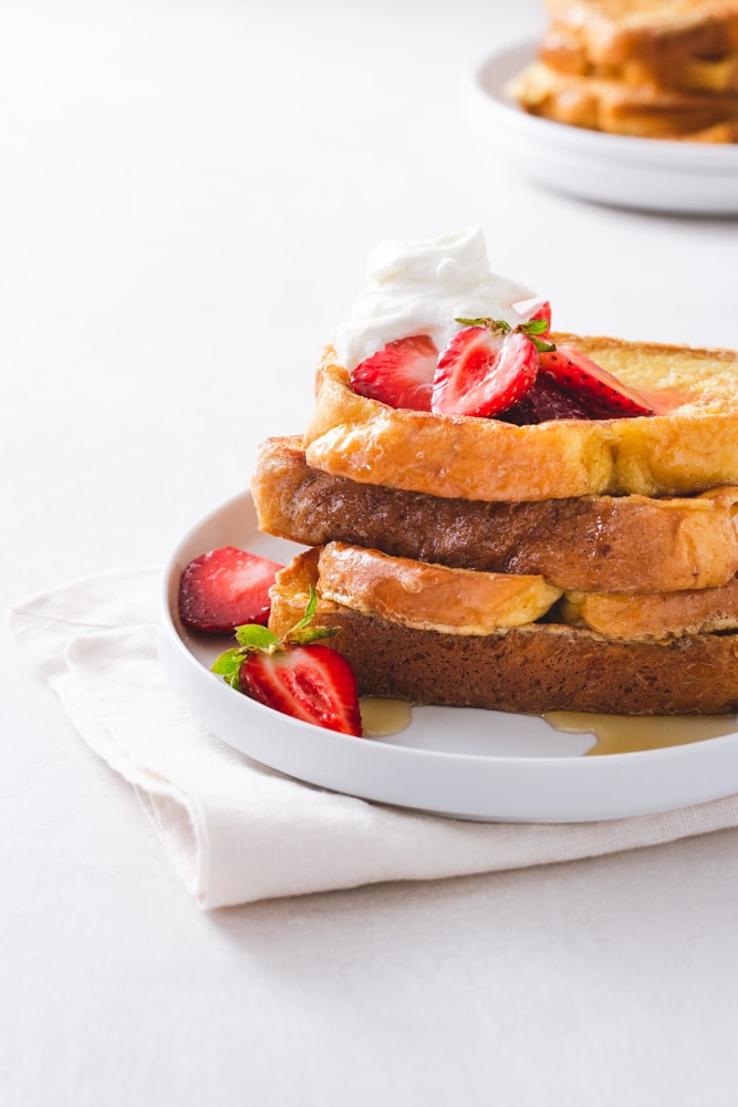Straight on view of a stack of Brioche French Toast topped with macerated strawberries and whipped mascarpone cream on a white plate on a napkin on a white surface with a plate of more French toast in the background.