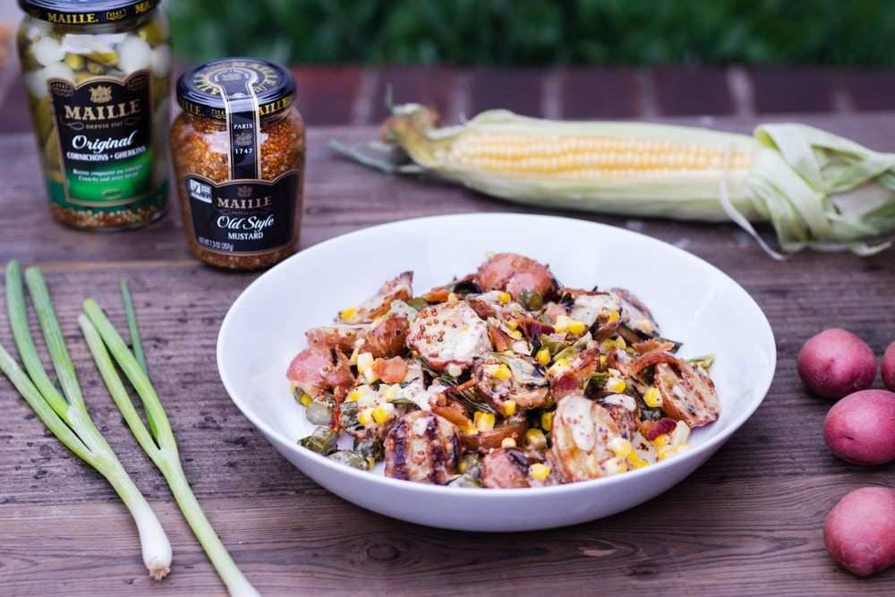 3/4 angled view of a bowl of Grilled Potato Salad with Charred Corn, Scallions and Bacon with a whole grain mustard dressing outside on a wooden table surrounded by the raw ingredients and plates.