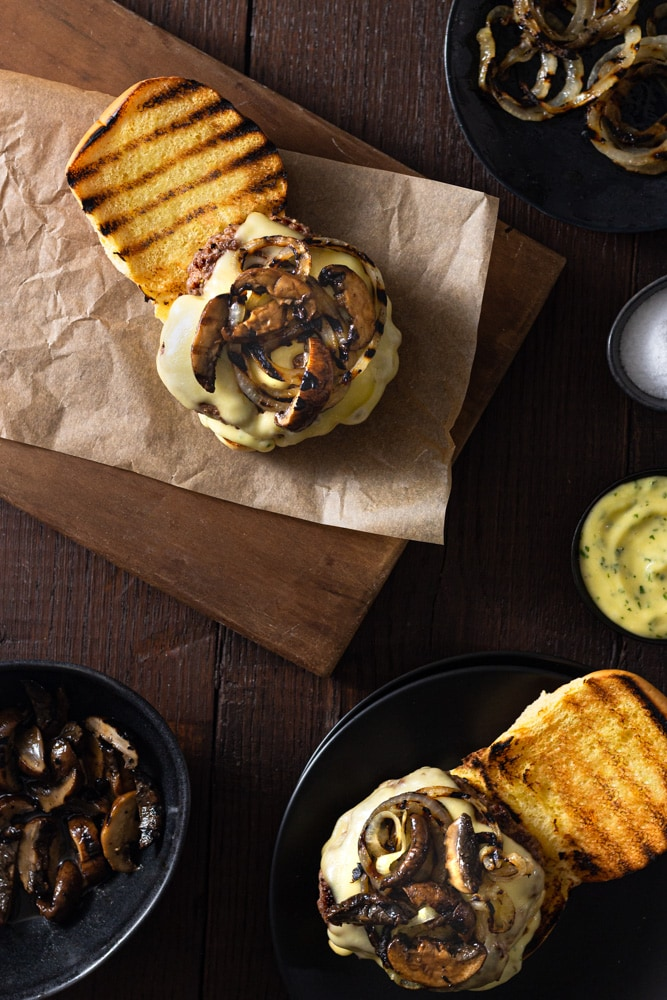 Overhead view of two Mushroom Swiss Burgers with Tarragon Aioli and grilled onions on a cutting board on a dark wood surface surrounded by bowls of aioli, mushrooms, onions and salt.