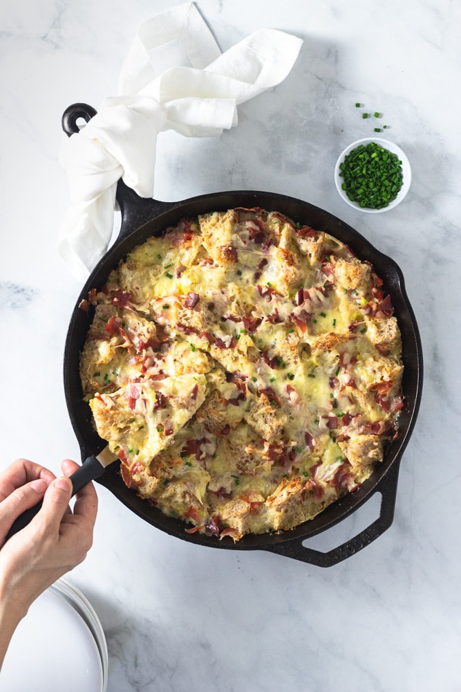 Overhead shot of a slice being lifted out of a Ham and Cheese Strata made with Bayonne Ham in a cast iron pan on a marble surface surrounded by a bowl of chopped chives and a stack of white plates.