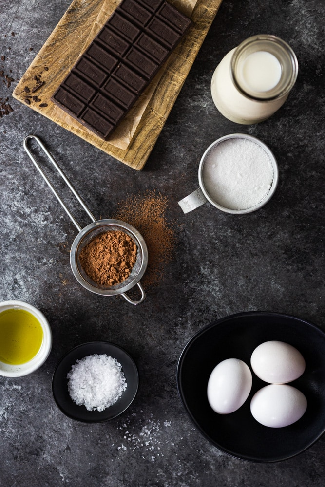 Overhead shot of ingredients for salted chocolate olive oil ice cream on a dark grey textured surface.