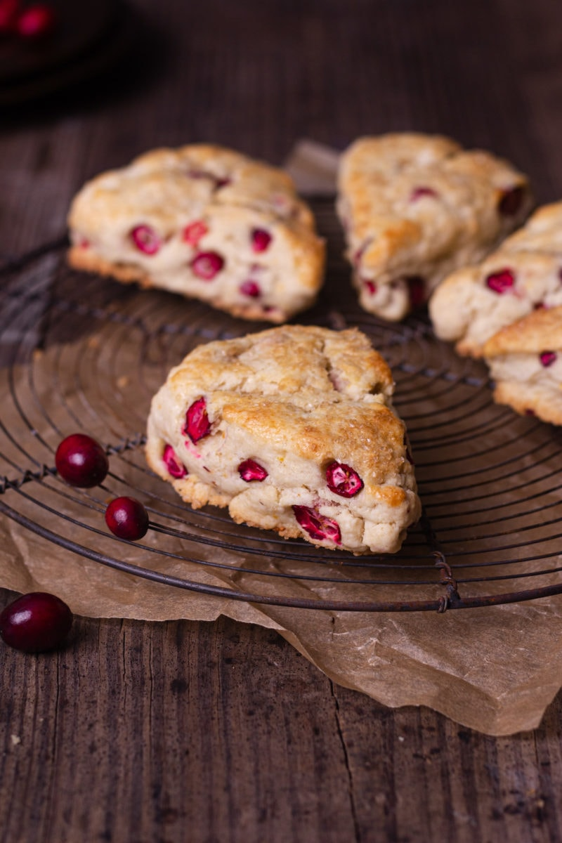 Straight on shot of Cranberry Orange Scones on a round wire rack on a rustic wood surface with a few fresh cranberries scattered around.