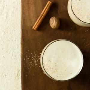 Overhead shot of two glasses of eggnog topped with fresh nutmeg on a wooden cutting board.