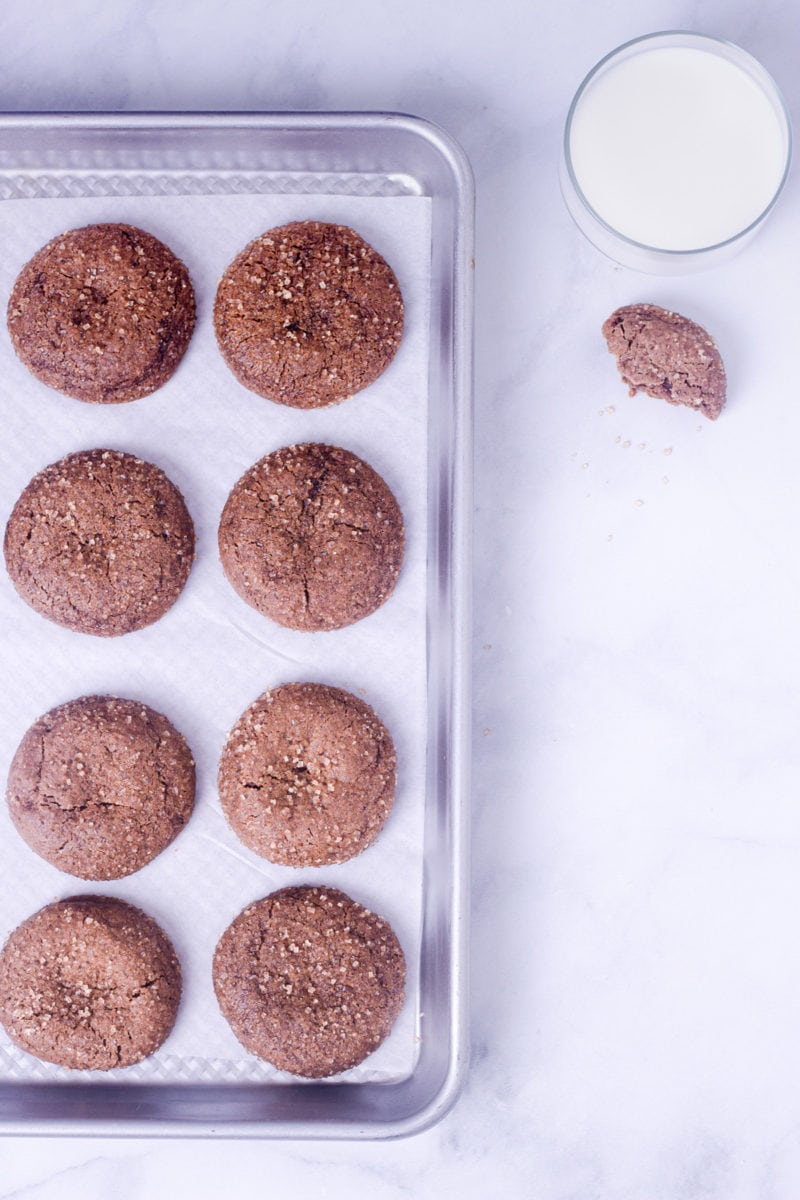 Chewy Ginger Molasses Cookies on a baking sheet, on a marble surface next to a glass of milk.