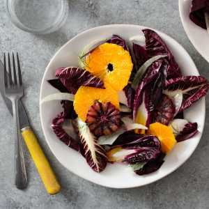 Orange and Fennel Salad with Radicchio on a white plate surrounded by a glass of water, a fork and a knife.