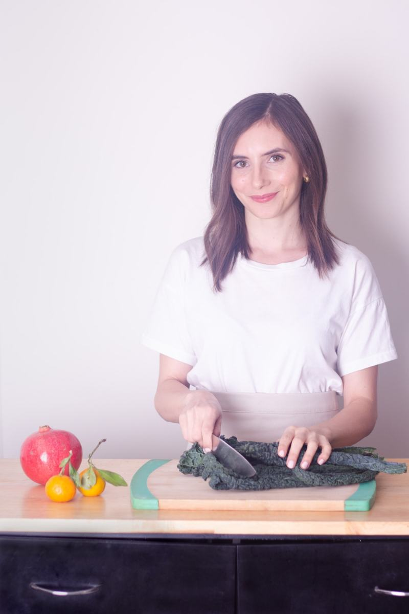 Food blogger, Sabrina Russo, cutting kale on a counter top.