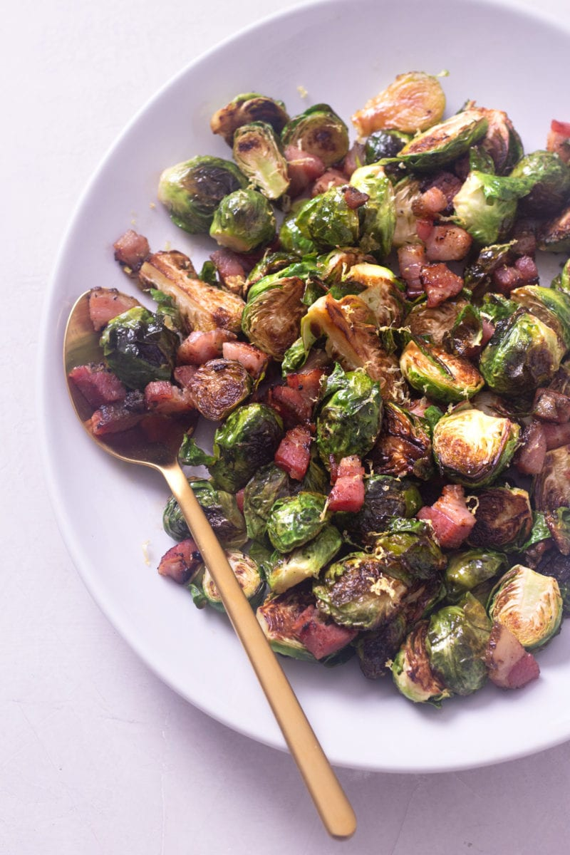 Pan roasted brussels sprouts with pancetta on a white serving platter with a copper spoon on a light surface.
