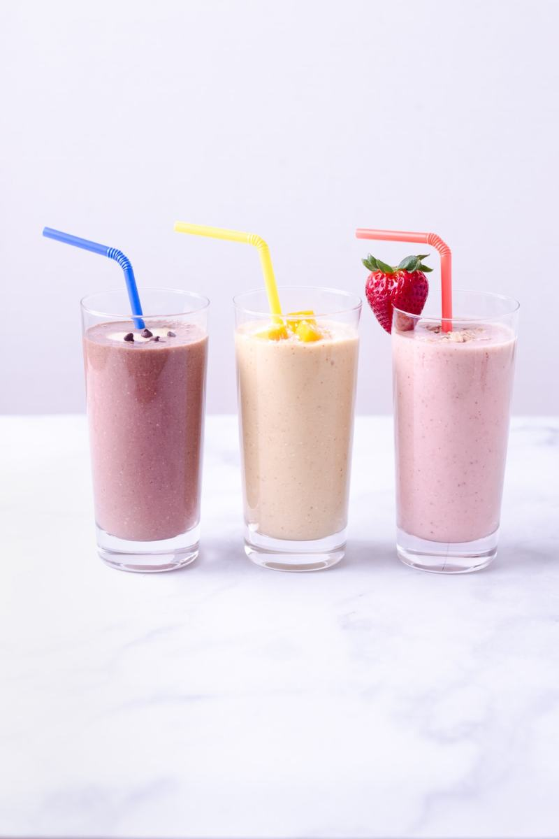 Straight on shot of three breakfast oatmeal smoothies in a line on a marble surface: strawberry banana, turmeric coconut mango, chocolate peanut butter.