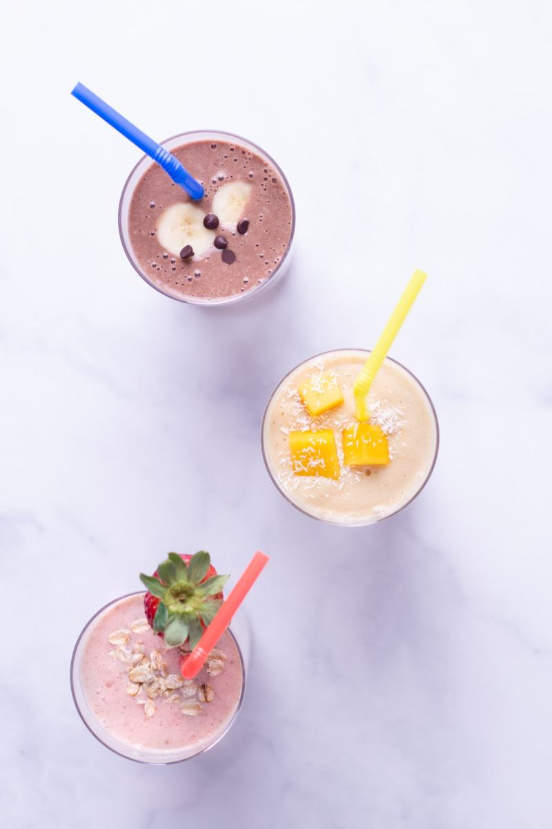 Overhead shot of three breakfast oatmeal smoothies in a triangle pattern on a marble surface: strawberry banana, turmeric coconut mango, chocolate peanut butter.