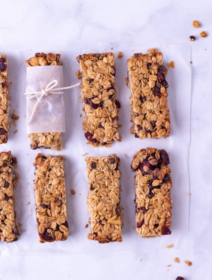 Overhead view of granola bars with walnuts, chocolate chips and dried cranberries lined up in two rows on a marble surface.