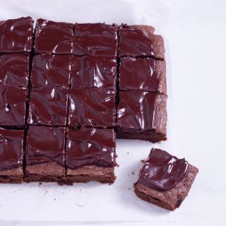 Slightly angled above view of fudgy, sliced red wine brownies with ganache.
