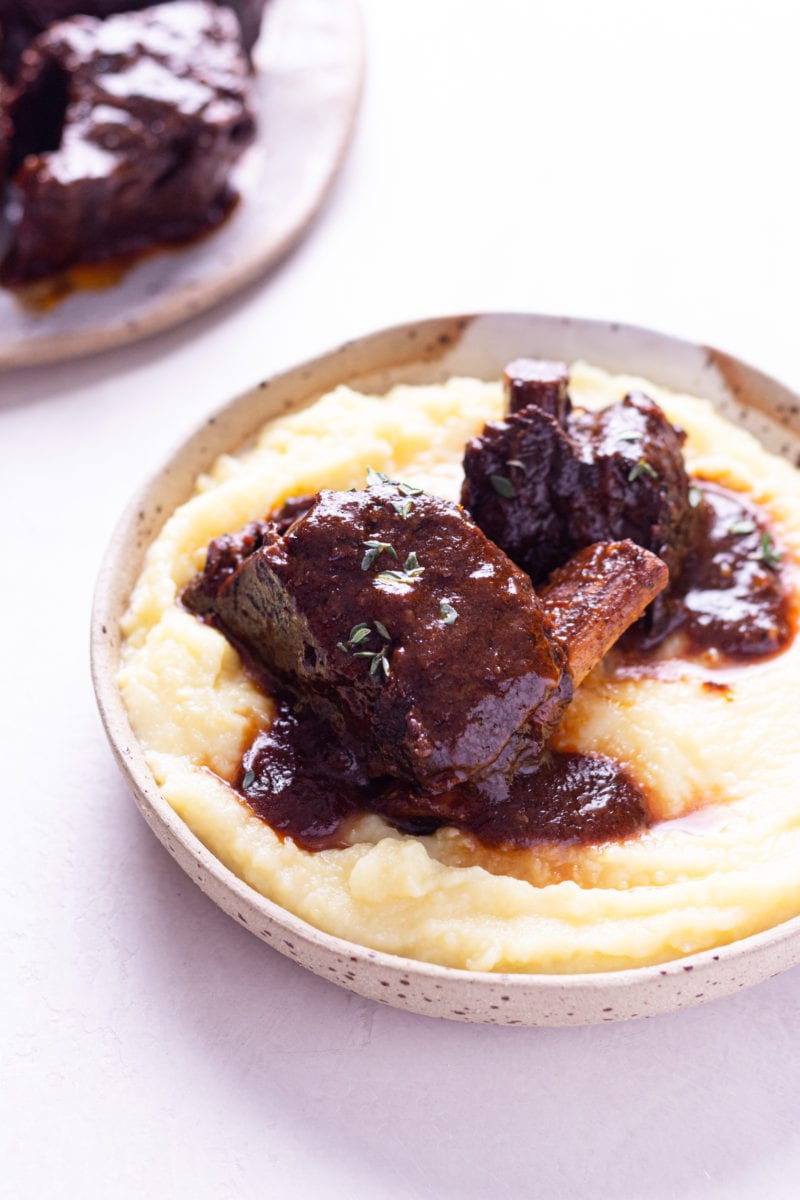 Angled view of a shallow bowl of mashed potatoes topped with Instant Pot Short Ribs with a red wine tomato sauce on an off white surface.