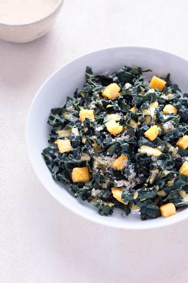 Angeled view of a bowl of Kale Caesar Salad with Polenta Croutons with caesar dressing in the background on an off white surface.