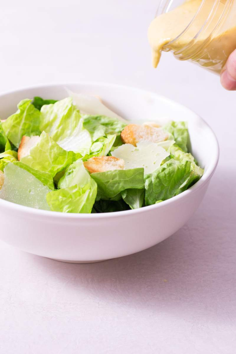 Dressing in a jar being poured over a bowl of Caesar Salad on a white surface.