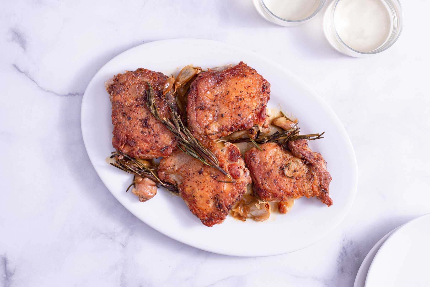 Overhead shot of a platter of Crispy Chicken Thighs with Rosemary and Garlic surrounded by glasses of wine and white plates on a marble surface.