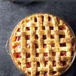 Strawberry Rhubarb Pie overhead on dark grey surface.