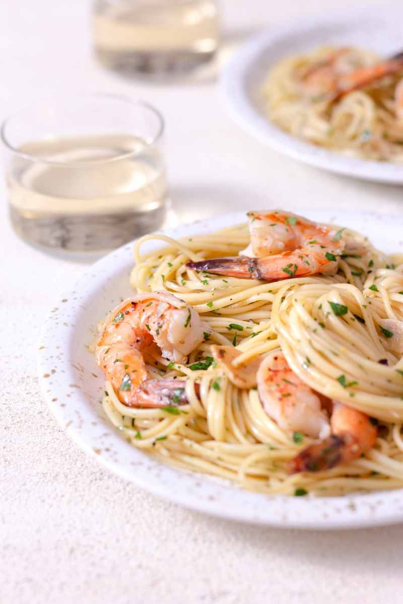 Angled view of a plate of shrimp pasta with wine glasses and another plate in the background on a white plaster surface.