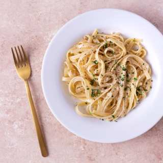 Overhead, close up view of a plate of Fettuccine Alfredo garnished with parsley surrounded by a copper fork and a bowl of grated parmesan cheese on a light brown, textured surface.