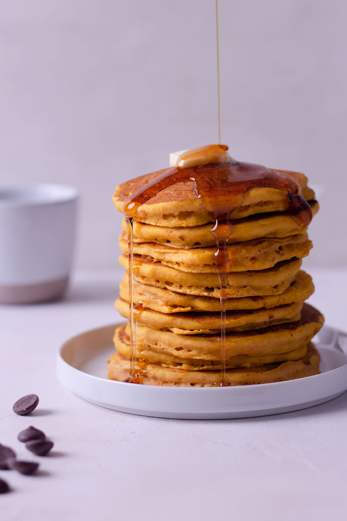 Straight on shot of a high stack of pumpkin chocolate chip pancakes with butter on top and maple syrup dripping down, with a coffee mug in the background.
