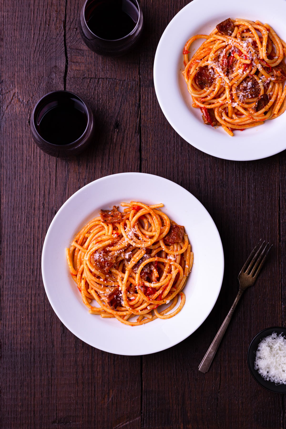 Two bowls of pasta with Amatriciana sauce topped with grated pecorino cheese, surrounded by glasses of red wine and a fork.