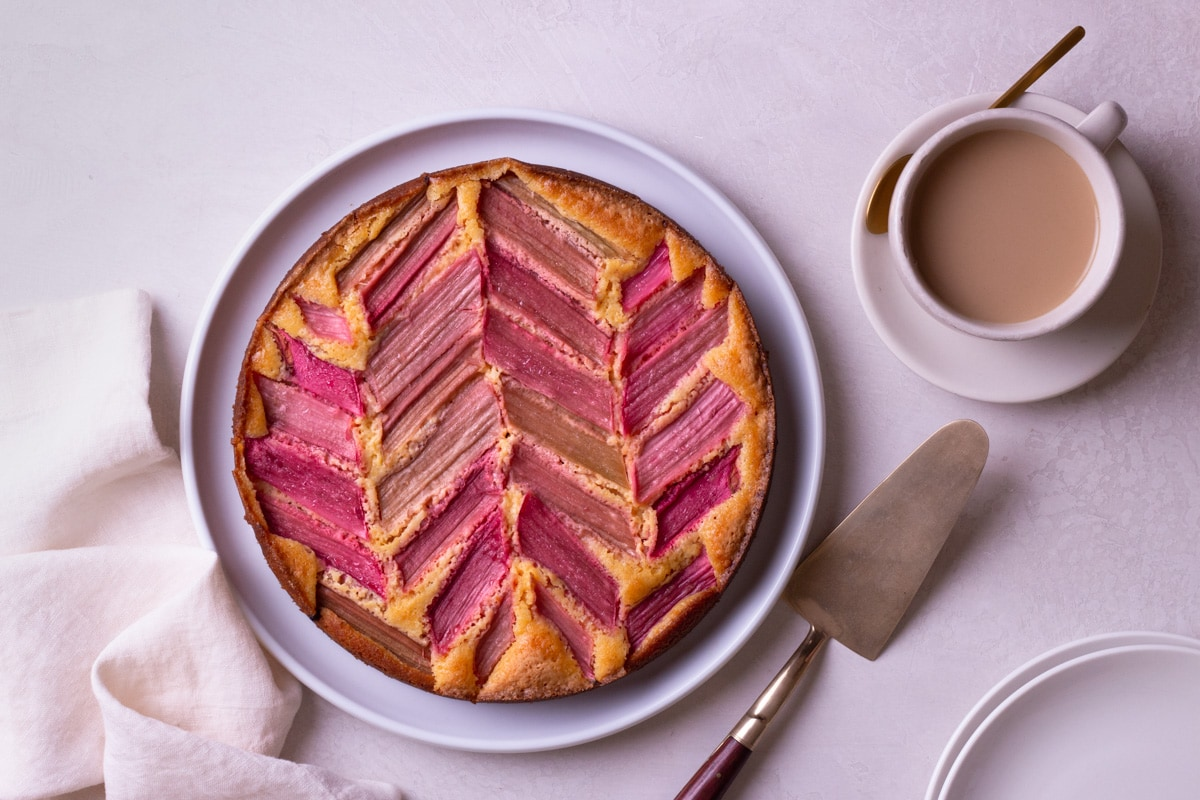 Overhead shot of a rhubarb cake on a cream surface surrounded by a cake knife, cup of coffee, plates and dish towel.