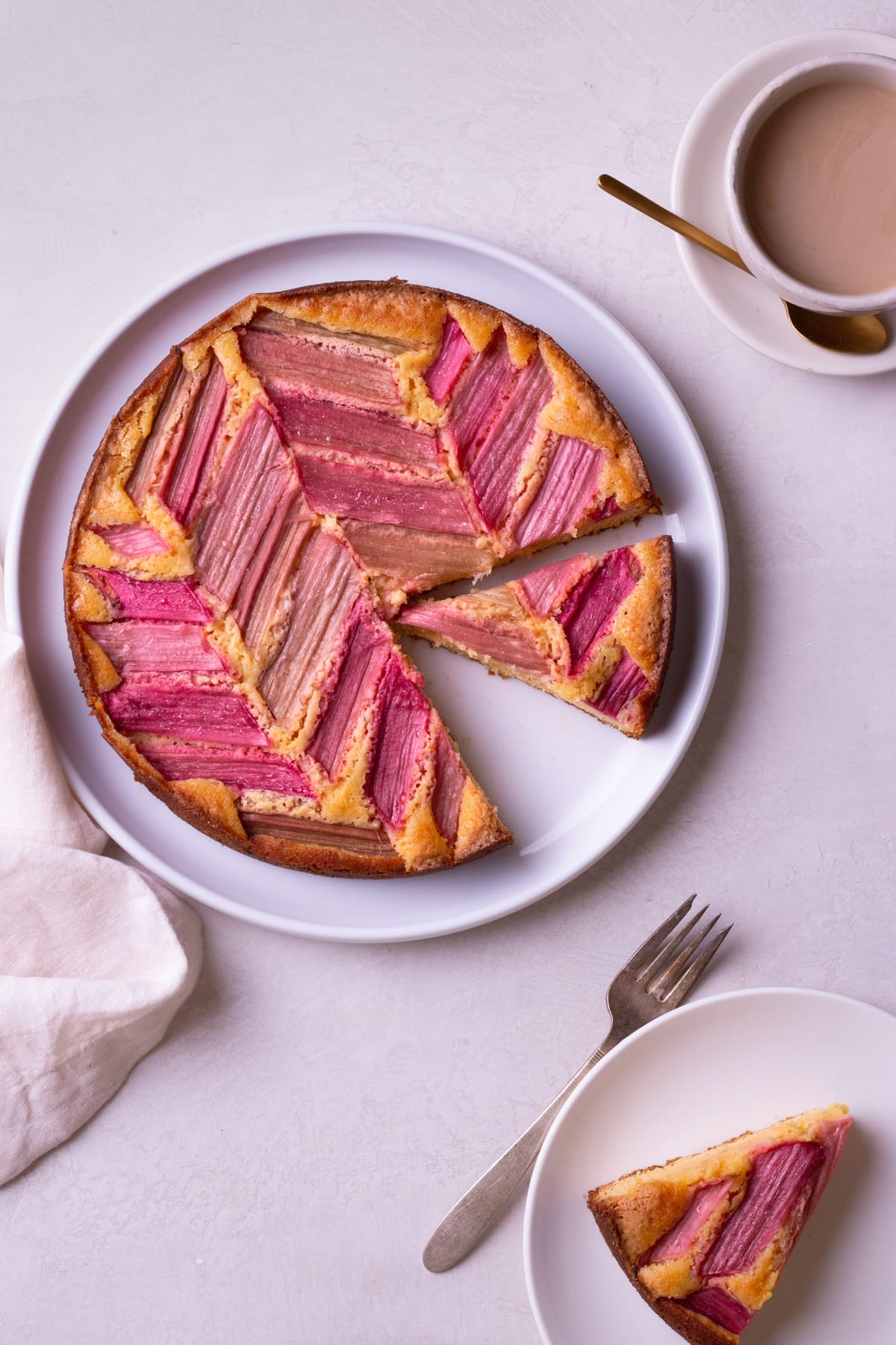 Overhead view of Rhubarb Custard Cake with slices cut out of it on a cream surface surrounded by a cup of coffee and a slice of cake.